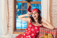 Beautiful woman in pajamas with gift box, window in the background.