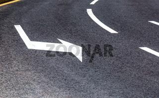 Traffic sign white arrow on asphalt road