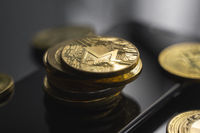 Stack of golden Monero bitcoin coin on a smartphone with a lot of bitcoins coins on a table. Virtual cryptocurrency concept. Mining of bitcoins online bussiness. Bitcoins trading.