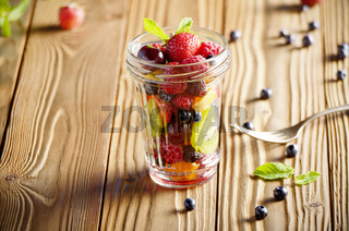 Assorted berries in mason jar on kitchen wooden table with fork aside