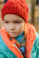 Little girl with red hat and green jacket close-up