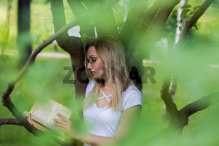 Young woman holding a book in hands leaning on a tree branch
