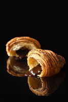 Croissant with chocolate flowing out on a black background