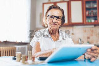 Senior woman at home checking her finances and invenstments