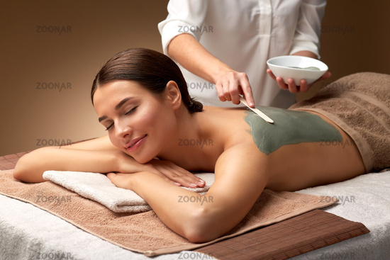 woman and cosmetologist applying clay mask in spa
