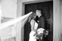 The kiss. Groom kisses bride on forehead in front of church portal.