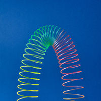 Flexible plastic rainbow spring on a blue background.