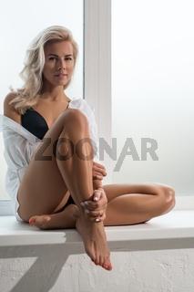 Gorgeous blonde in underwear on a window sill