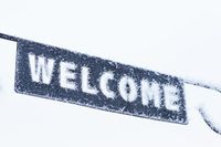 Welcome sign close-up covered in frost