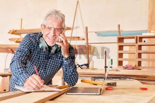 Senior Handwerker mit Checkliste und Handy