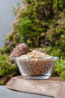 Peeled pine nuts in a glass bowl on a natural background. Vertical frame.