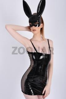 Sexy, vollbusige Rothaarige, gekleidet in einem glanzenden schwarzen PVC-Kleid und Kaninchen Maske