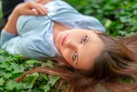 Young beautiful girl with perfect skin and makeup is lying down on ivy meadow, in spring park scenery, looking at the camera. Gorgeous woman outdoors enjoying nature. Healthy lady on green background