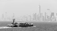 Freight tug pushing cargo ship to the port in New York City and Lower Manhattan skyscarpers skyline in background.