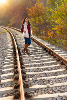A gorgeous romantic young woman standing on the railroad tracks and looking sadly at the camera, in fall scenery outdoors. Full length shot in beautiful autumn natural light, with sun from behind