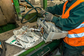 Bucharest, Romania - October, 2013: Worker disassembling used electronic printing machines and preparing them to be recycled on a recycling plant