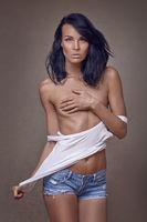 Hübsche brünette Frau bedeckt ihre Brust mit der Hand