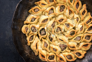 Traditional Armenian manti oven backed with mincemeat as top view in a cast iron pan