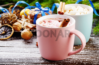 Christmas background of two mugs of hot chocolate with marshmallows, spruce branch and tray with gingerbread cookies on wooden table