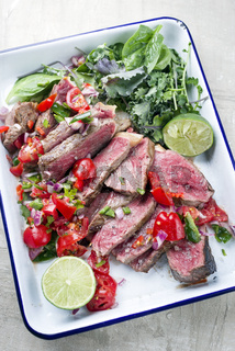 Traditional South American barbecue wagyu roast beef sliced with pico de gallo and salsa verde garnished with lettuce as top view in a rustic skilled