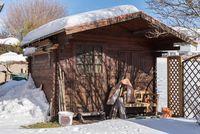 Schneebedeckte Holzhütte - Gartenlaube in Winterlandschaft