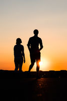 silhouette of boy and girl on sunset sky background