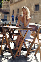 Beautiful young blond woman in blue summer dress sit at table at open air cafe outdoors restaurant smiling looking at camera, female hold in hand smartphone resting in old street town of Murcia, Spain