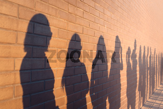 A line of shadows of people lined up against a red brick wall. Stand in a queue to the changes