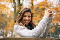 Woman laughing holding her mobile phone and looking at camera in Autumn city park.