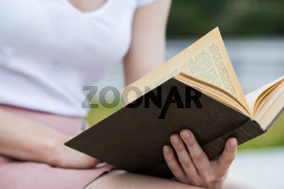Young woman holding an old book in her hands outdoors