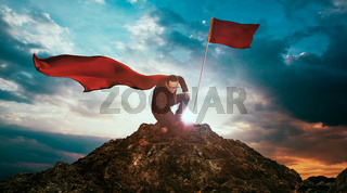 Businessman in a suit and cape hero on top of a mountain
