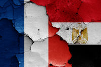flags of France and Egypt painted on cracked wall
