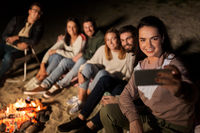 happy friends taking selfie at camp fire on beach