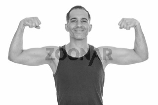 Mature happy Persian man flexing both arms getting ready for gym
