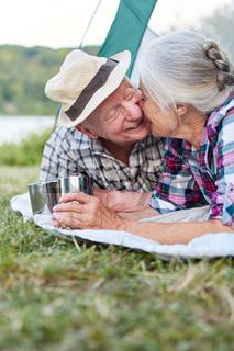 Senioren Paar gibt sich einen Kuss im Zelt