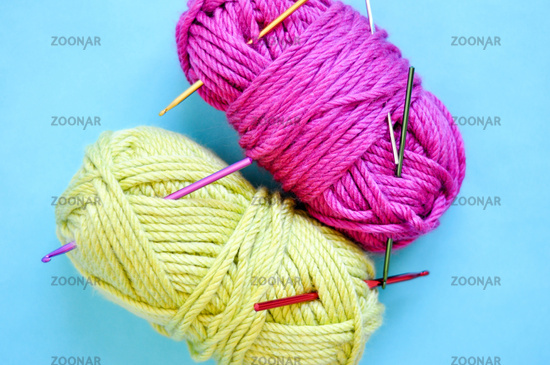 Green and pink yarn for knitting with spokes on blue background