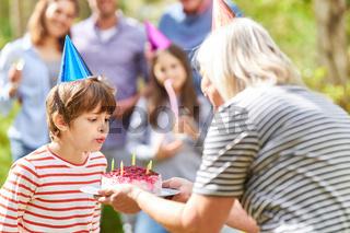 Junge pustet Kerzen aus auf seiner Geburtstagstorte