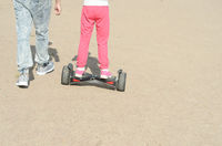 Back view of small girl driving on electric self-balancing scooter at sunny day.Walking on segway with friend.