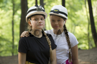 Two teen girls speleologists in helmets in the forest at sunny d