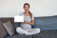 Junge schwangere Frau hält ein Tablet