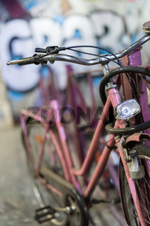 The attached old rundown bicycle in pink