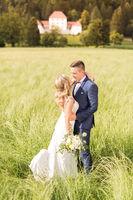 Newlyweds hugging tenderly in meadow in front of Strmol castle in Slovenian countryside.