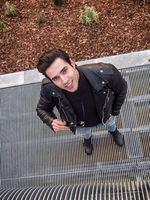 Young man on metal grid looking at camera