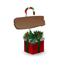 Festive composition with wooden board with candy and Christmas tree branches on a gift box decorated with bows on a white background.