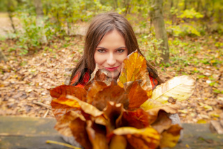 Gorgeous young woman outdoors, in a park autumn scenery, holding yellow leaves, looking at the camera and smiling. Close-up shot in natural light, retouched for perfect skin, vibrant colors