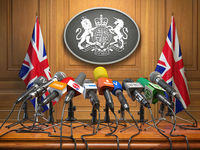 Briefing or press conference of prime minister or queen of UK  Great Britain. Microphones with flags of Great Britain and UK coat of arms.