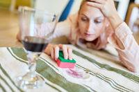 Hausfrau beseitigt mühsam den Rotwein Fleck