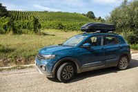Tourist car in vineyards. Rural tourism concept with car and wine grapes on background.