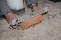 Maurer arbeitet mit Ziegelstein und Mörtel mit Hilfe einer Wasserwaage - Nahaufnahme
