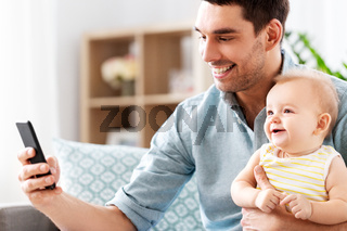 father with baby daughter using smartphone at home